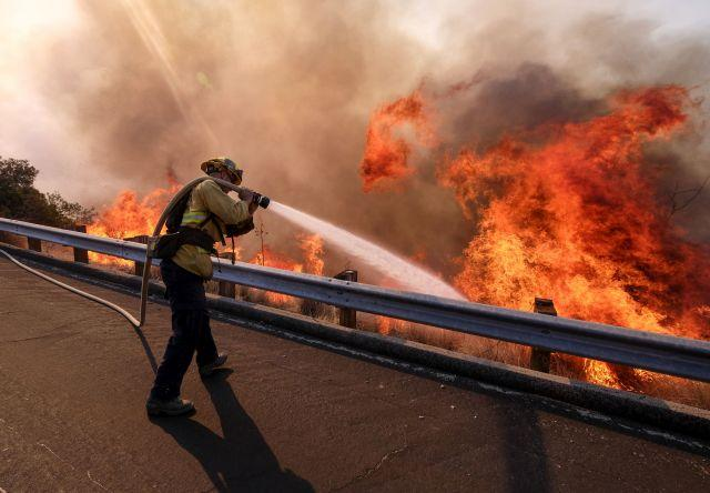 A firefighter battles a fire along the Ronald Reagan Freeway, aka state Highway 118, in Simi Valley, Calif. Photo by Ringo H.W. Chiu/AP