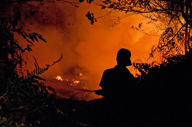 An officer is trying to extinguish fire in Kalimantan. Photo Credit: CIFOR