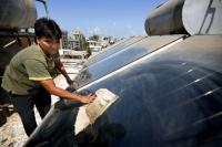 Wiping down rooftop solar panels in Mumbai. Flickr/The Climate Group