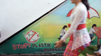 A woman passes by a mural on plastic ban. Photo credit: NPAP