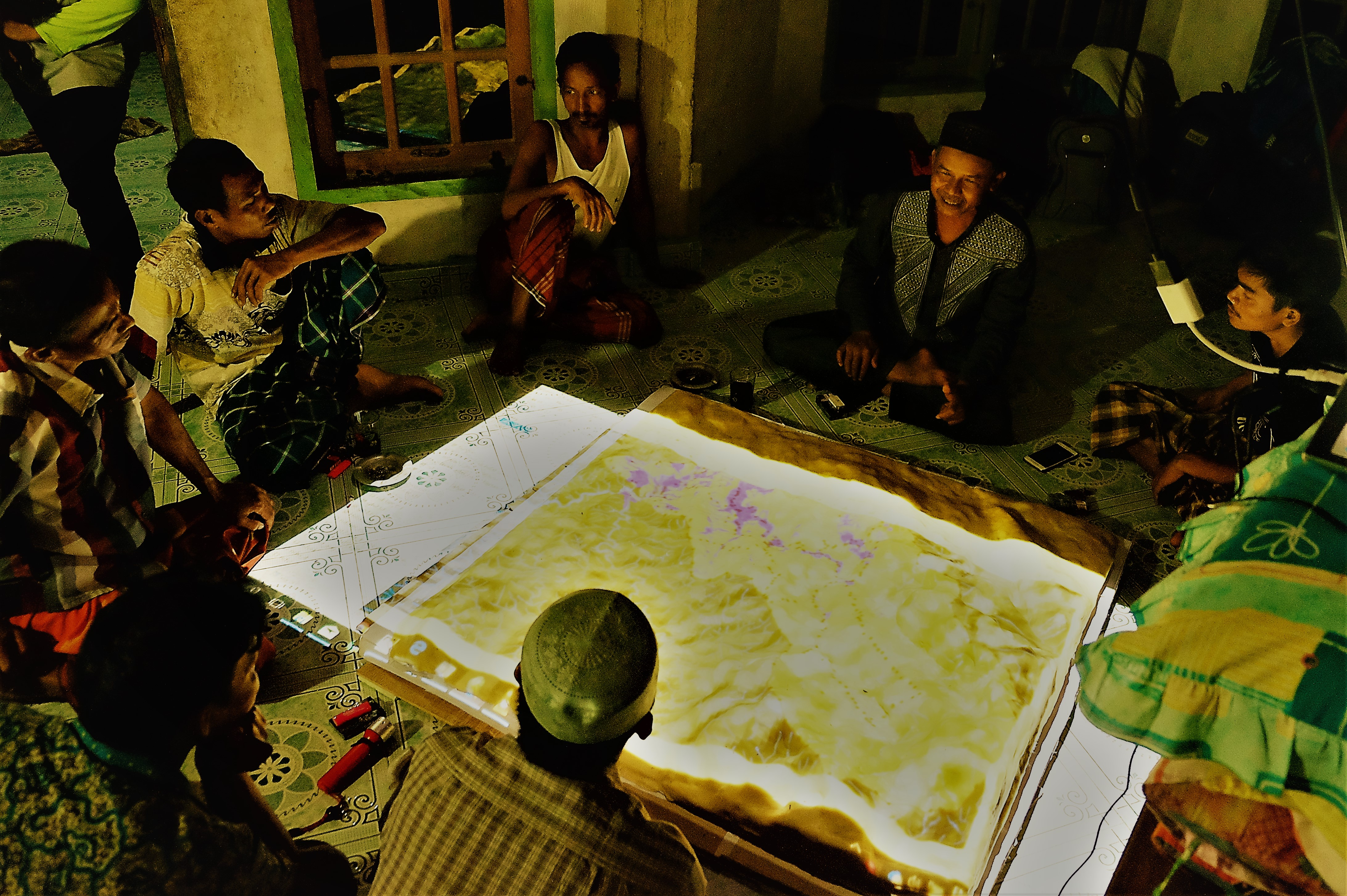 <p> Indigenous people in Gajah Bertalut, Kampar, Riau, observing 3D map models of their tribal lands. Photo by Julius Lawalata.</p>
